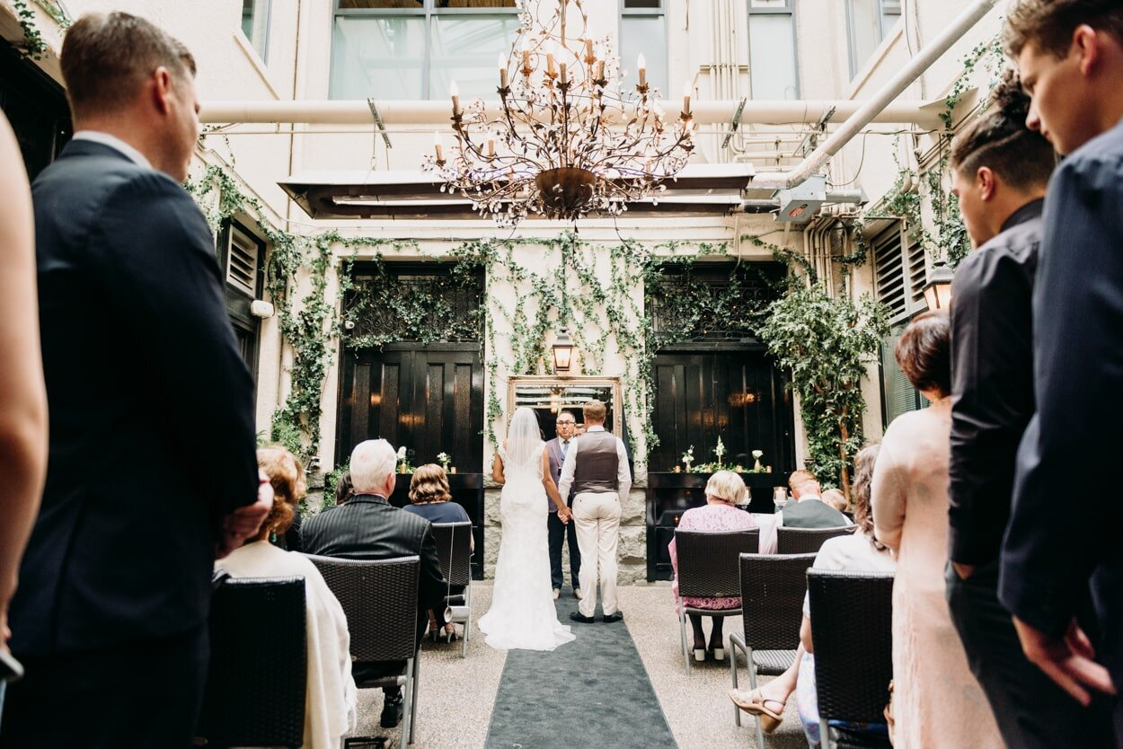 Bride and groom standing at end of aisle during wedding ceremony