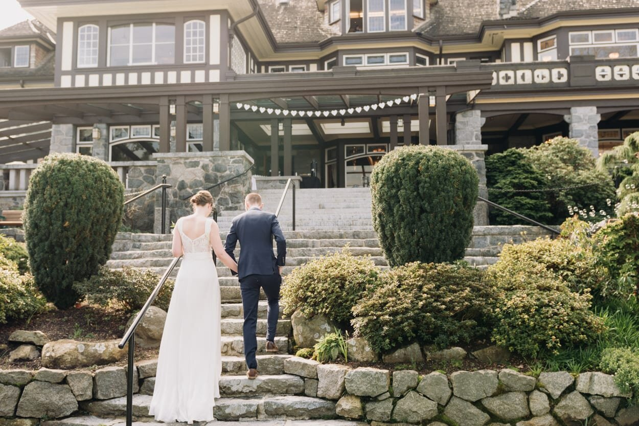 Bride and groom holding hands walking up stairs of large house