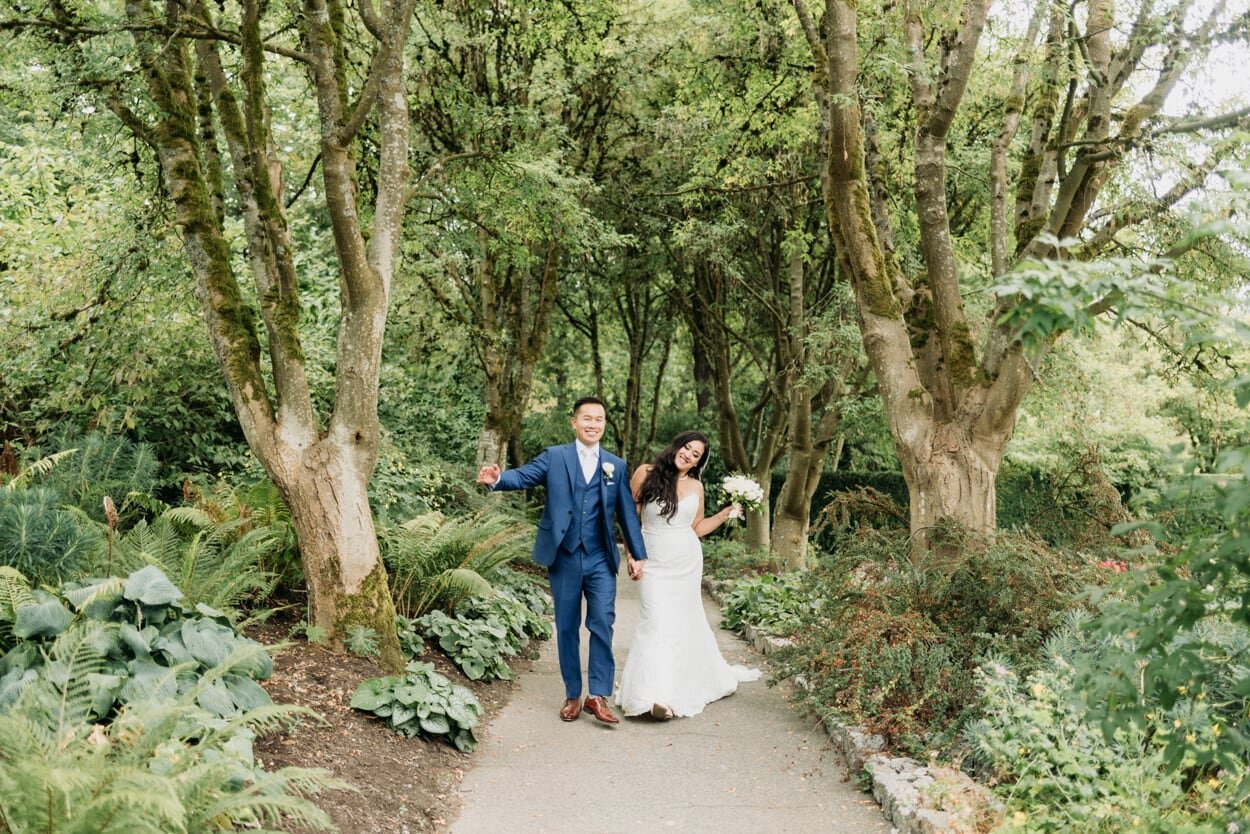 Bride and groom whimsically walking through a path of trees