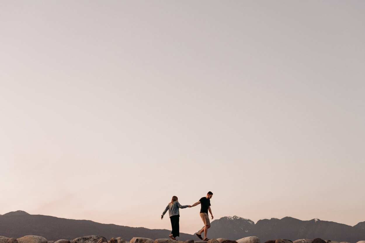 Couple holding hands walking on rocks with the mountains in background