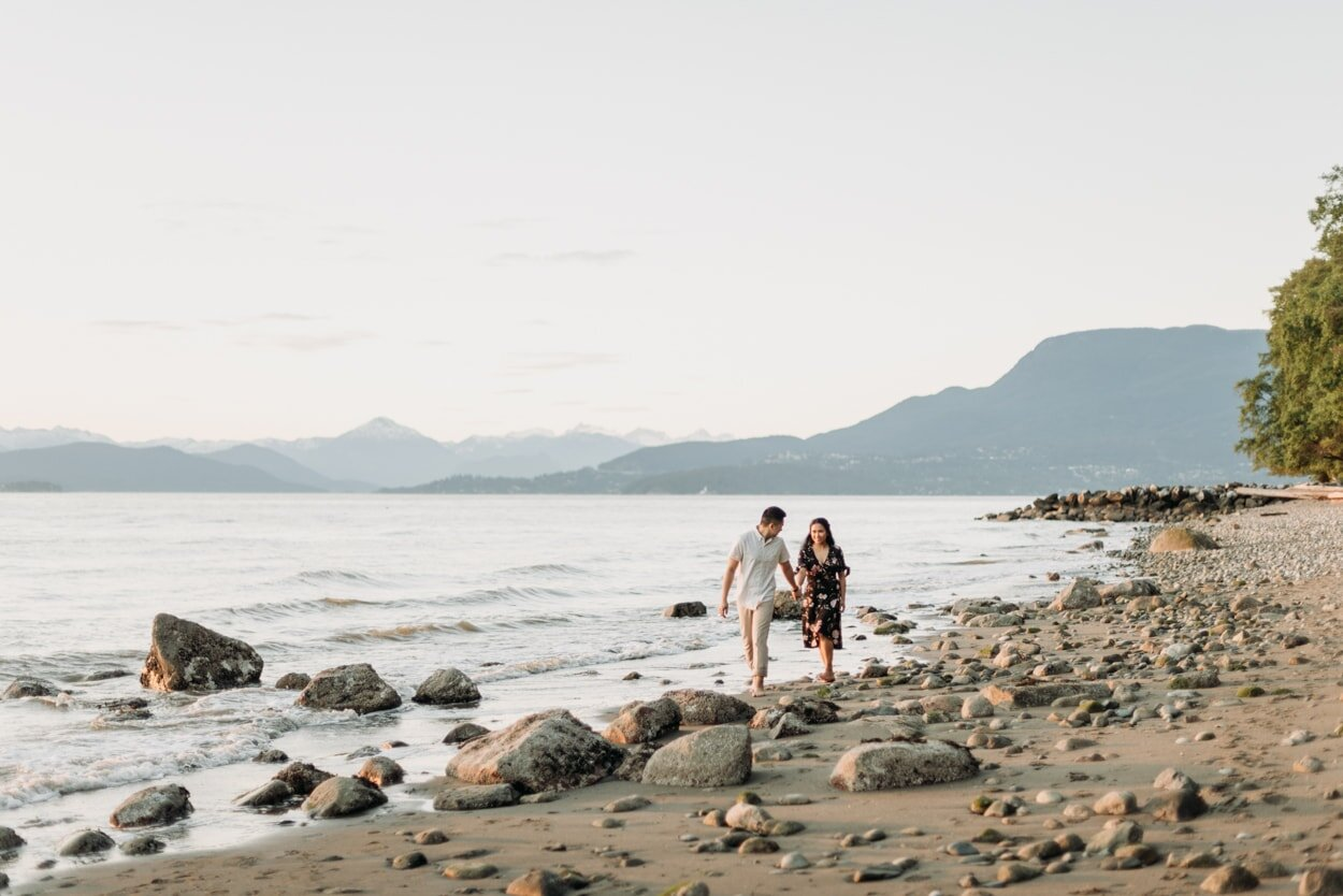 Man leading fiancee down the beach