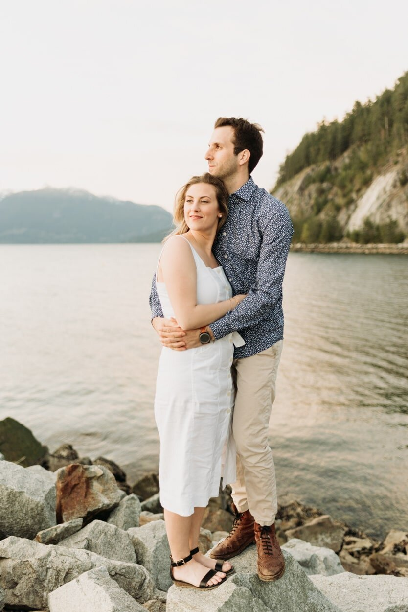 Couple holding onto each other while standing on a rock