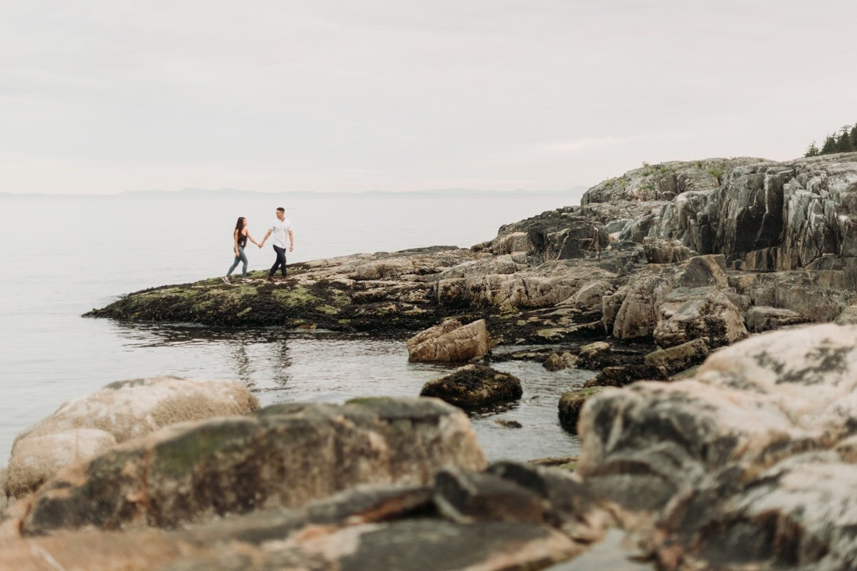 Couple walking on a rocky beach together holding hands