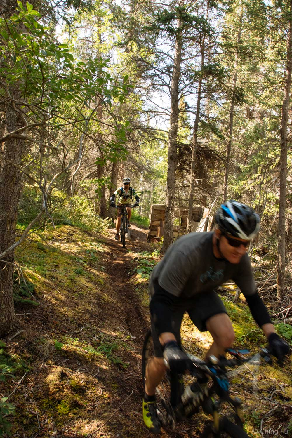 Riding past old wooden structures.