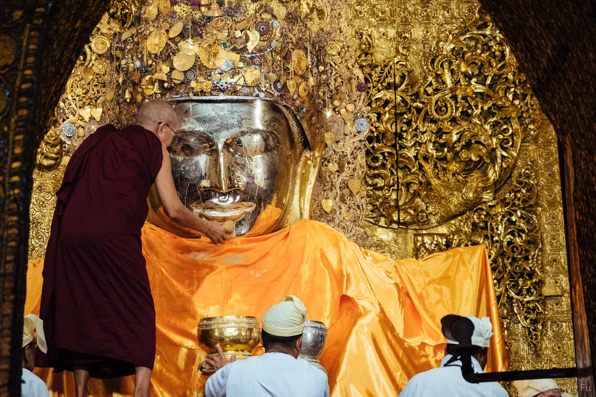 Gold leaves are frequently applied to Mahamuni Buddha by male devotees (only men are allowed in this room).