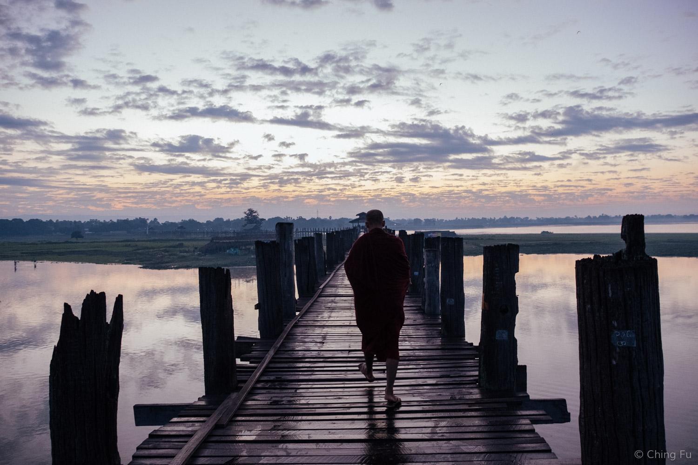 Monk walking on U Bein Bridge.