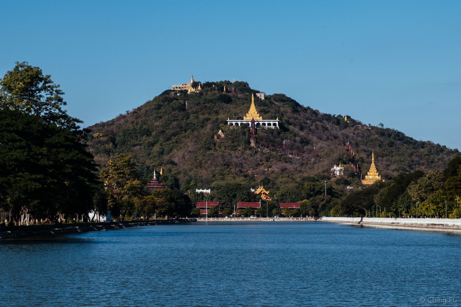 View of Mandalay Hill from Mandalay Palace's moat. In between the lower two golden spires, you can see the red covered stairway that brings visitors to the summit of Mandalay Hill.