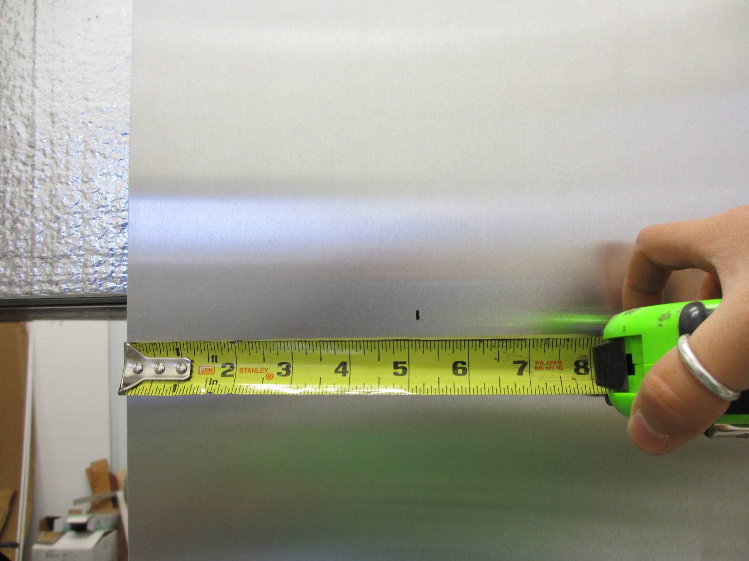 We measured where the next sheet needed to overlap the current sheet. This ensured that both sheets would be screwed into wood studs when we formed the seam.