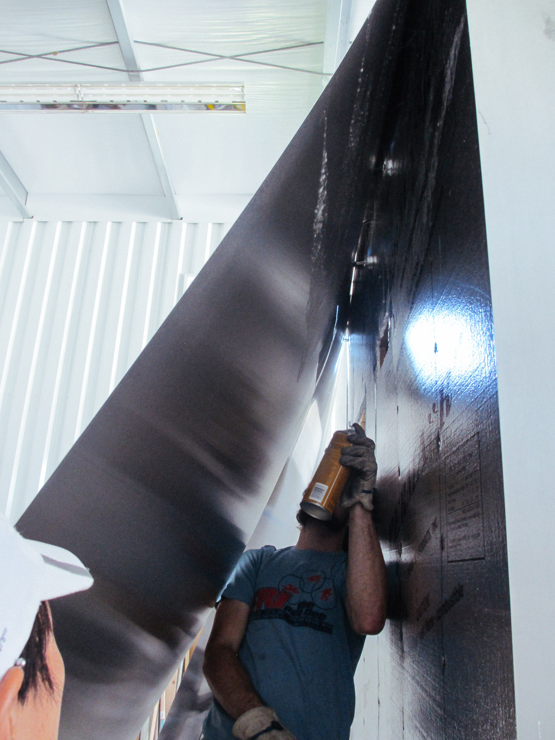 Adhesive was sprayed on the back of the aluminum sheets to attach to the foam insulation boards.