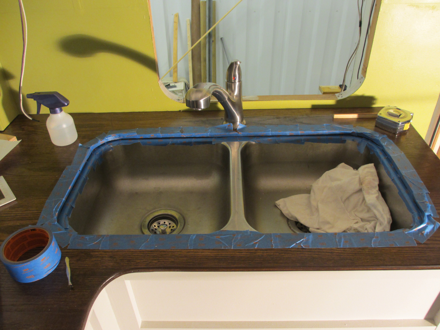 The countertop and kitchen sink were taped off for caulking.