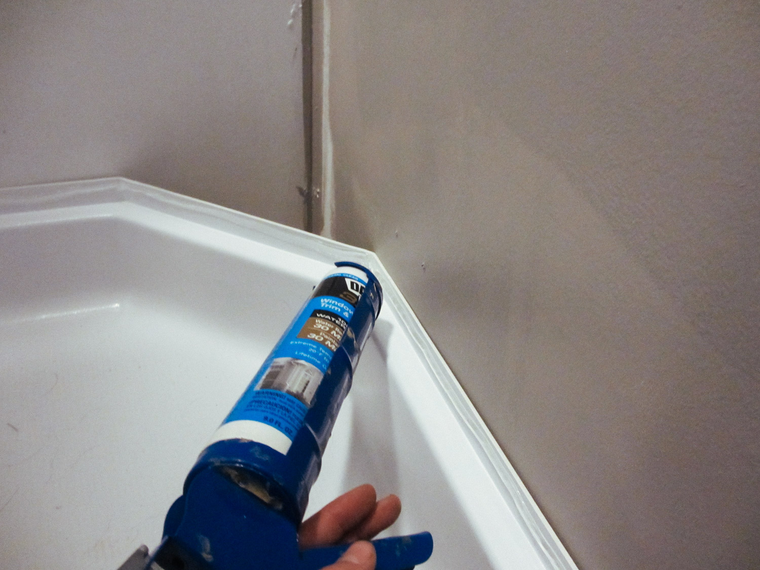 We caulked the top of the shower pan so it would adhere to the shower walls.