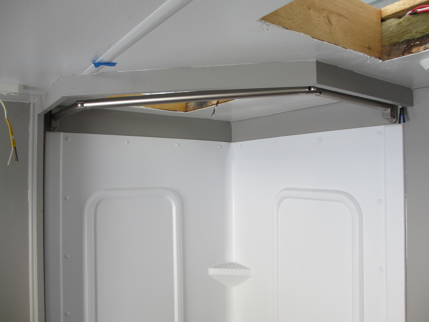"""We installed a hinged curtain rod behind the shower """"valance""""."""