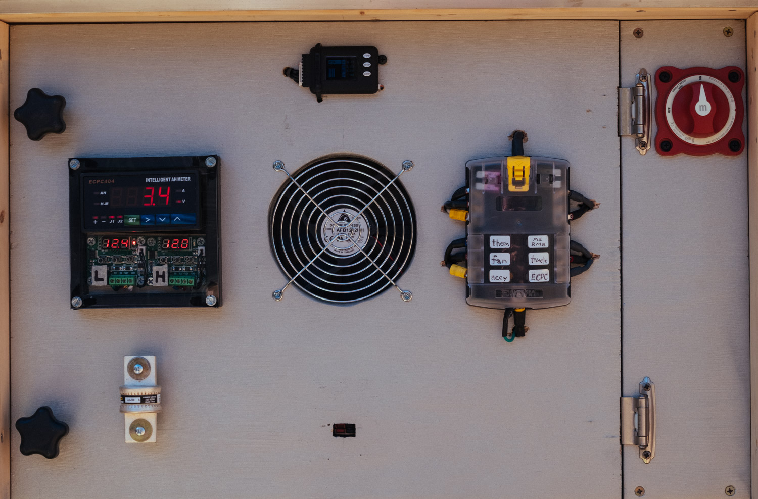 """This is the front view of the updated """"BMS panel"""" with (left to right): relay controller, thermostats, cell voltage monitor, cooling fan, fuse block, and battery disconnect switch. The spare fuse doubles as a handle."""