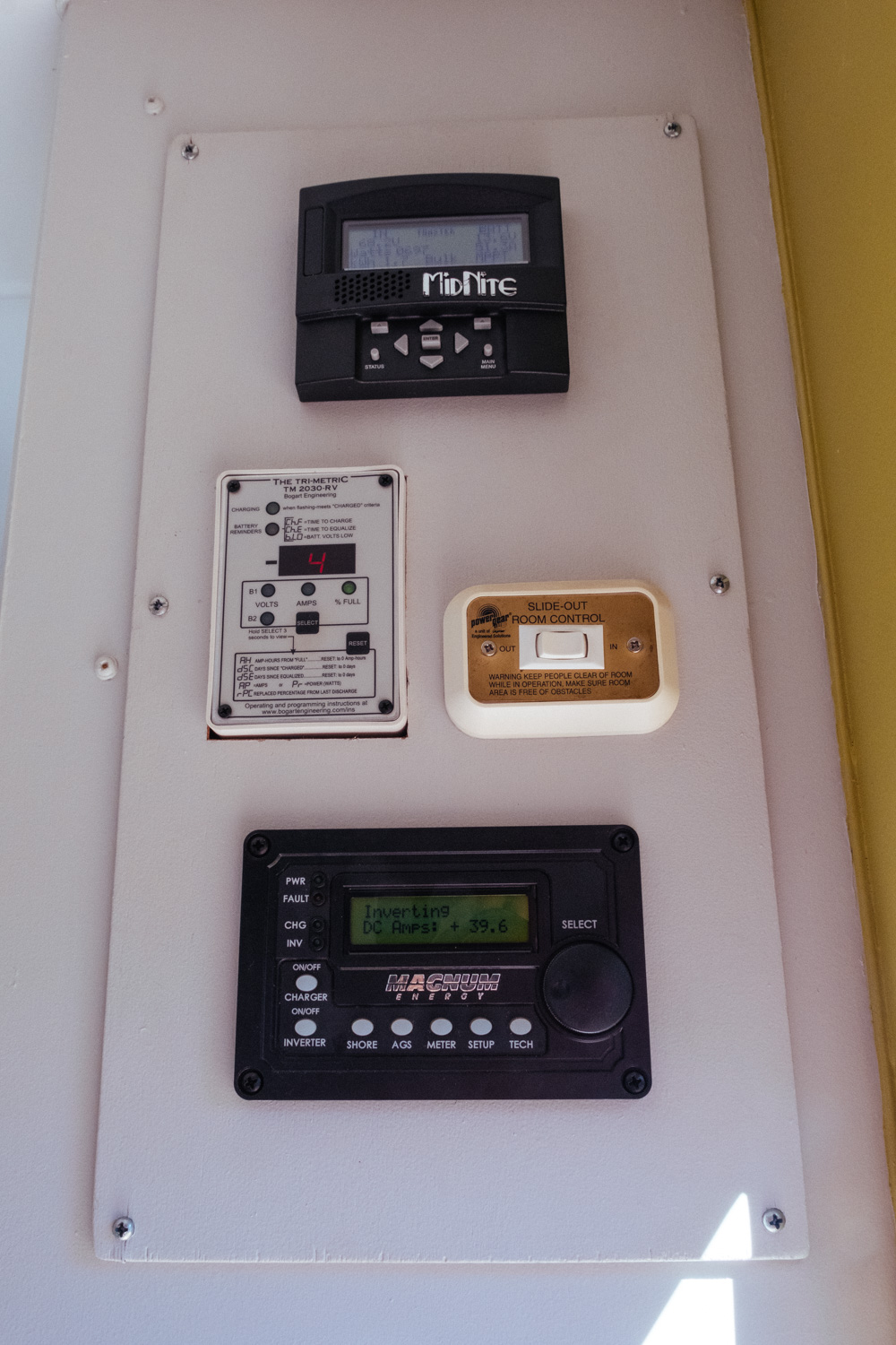 This is our current control panel layout (top to bottom): Midnight Solar remote display, Trimetric battery monitor, slide control, and Magnum inverter remote.