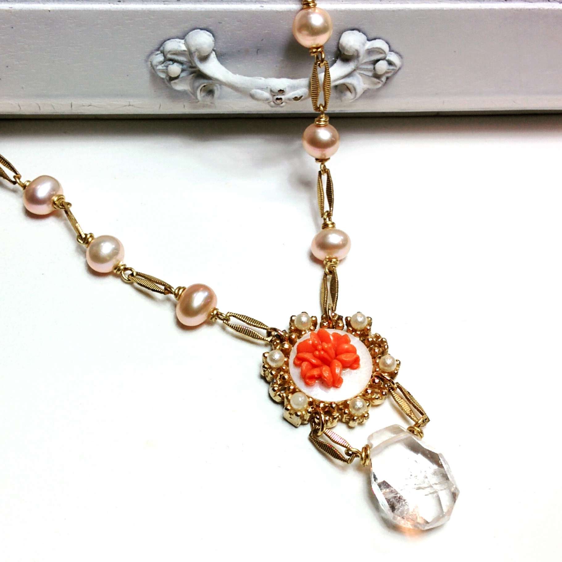 A beautiful crystal quartz stone fastened to a refurbished vintage treasure featuring a carved coral flower. Chain made using fresh water pearls and vintage components.