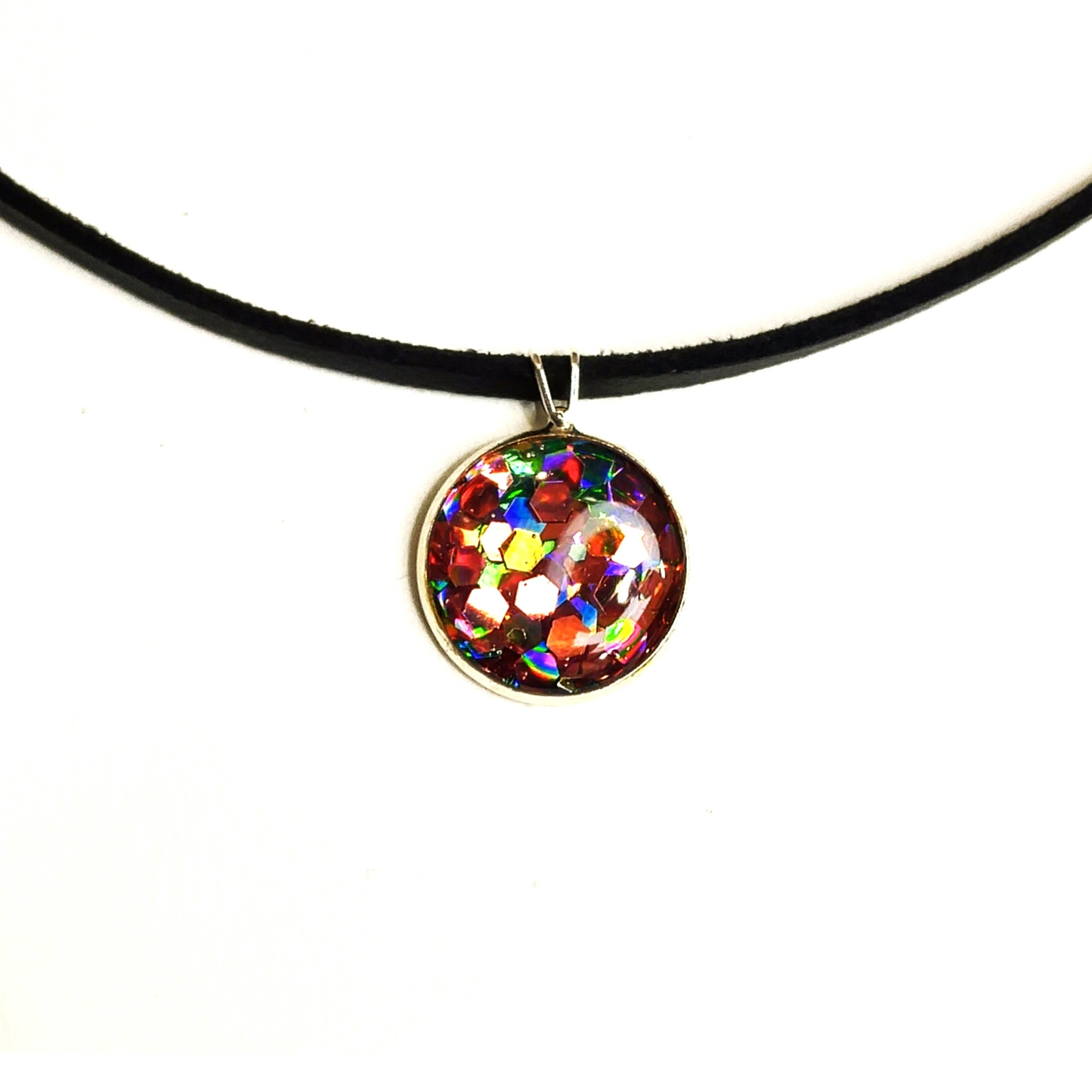 1/2 pendant containing rainbow inducing layers of hexagonal sparkles, set in resin is fun for all involved.