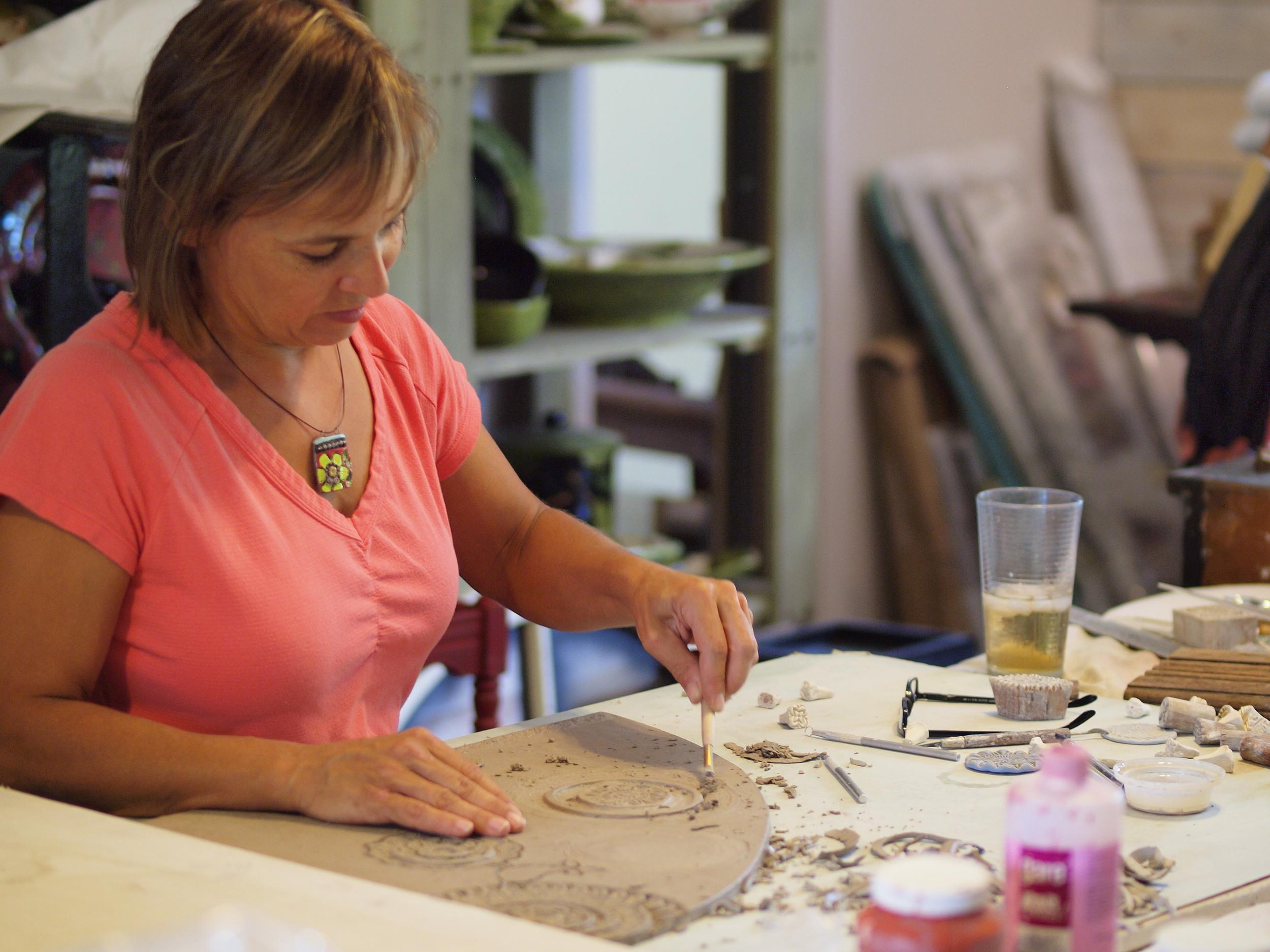 Clare working on raw clay slab
