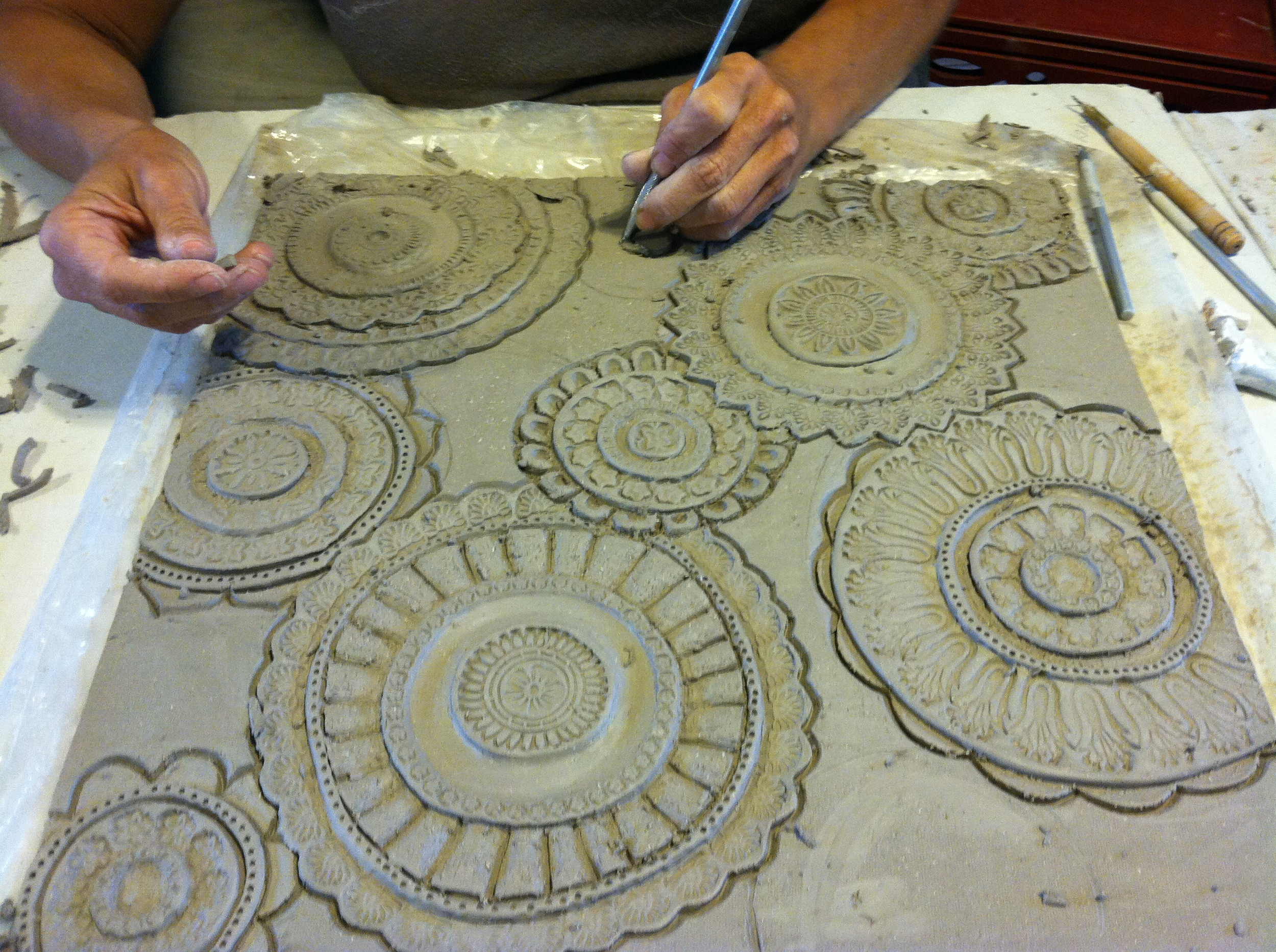 The design on each piece is freehand drawn. Then the texture is carved and stamped into the clay.