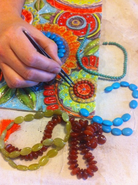 Setting in the semiprecious stones and beads to create the mosaic.