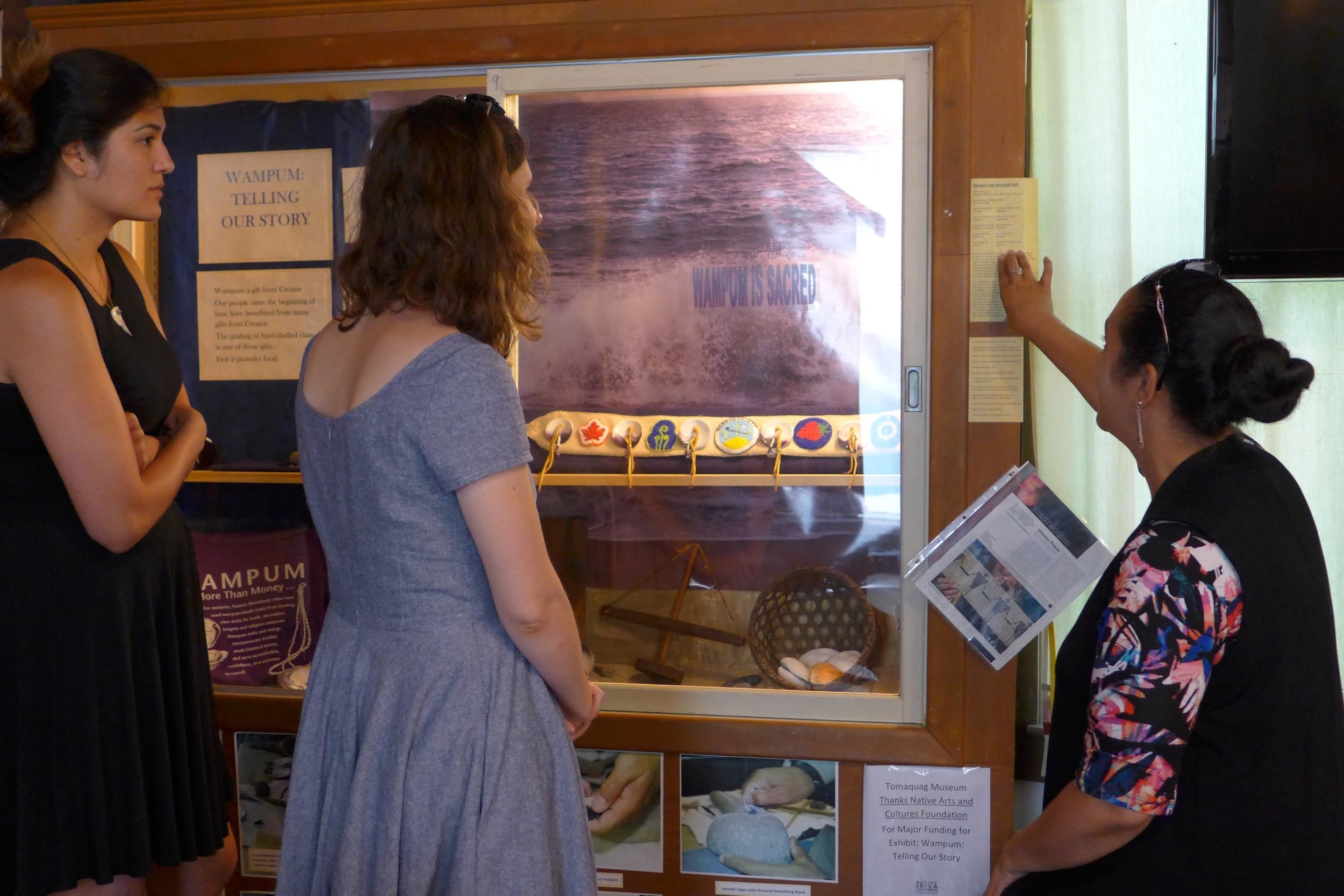 [caption] Stephanie Mach, Lise Puyo, and Lorén Spears looking at the wampum belt made by Narragansett community members under the creative direction of Allen Hazard. Photo by Margaret Bruchac.