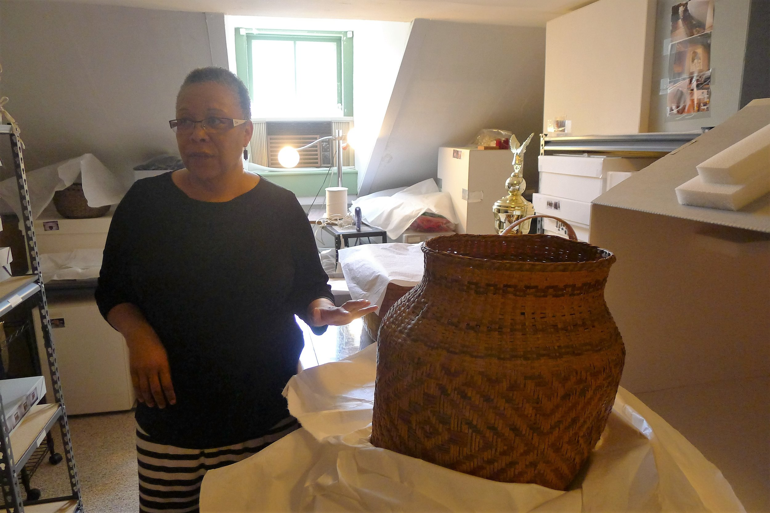 [caption] Kimberly Peters shares community connections of a cane basket given to Eva Lutz Butler by Dr. Frank Speck in 1945. The basket was given to Princess Redwing (Narragansett) by Mrs. Butler for the museum. Both were students of Frank Speck. Photo by Margaret Bruchac.