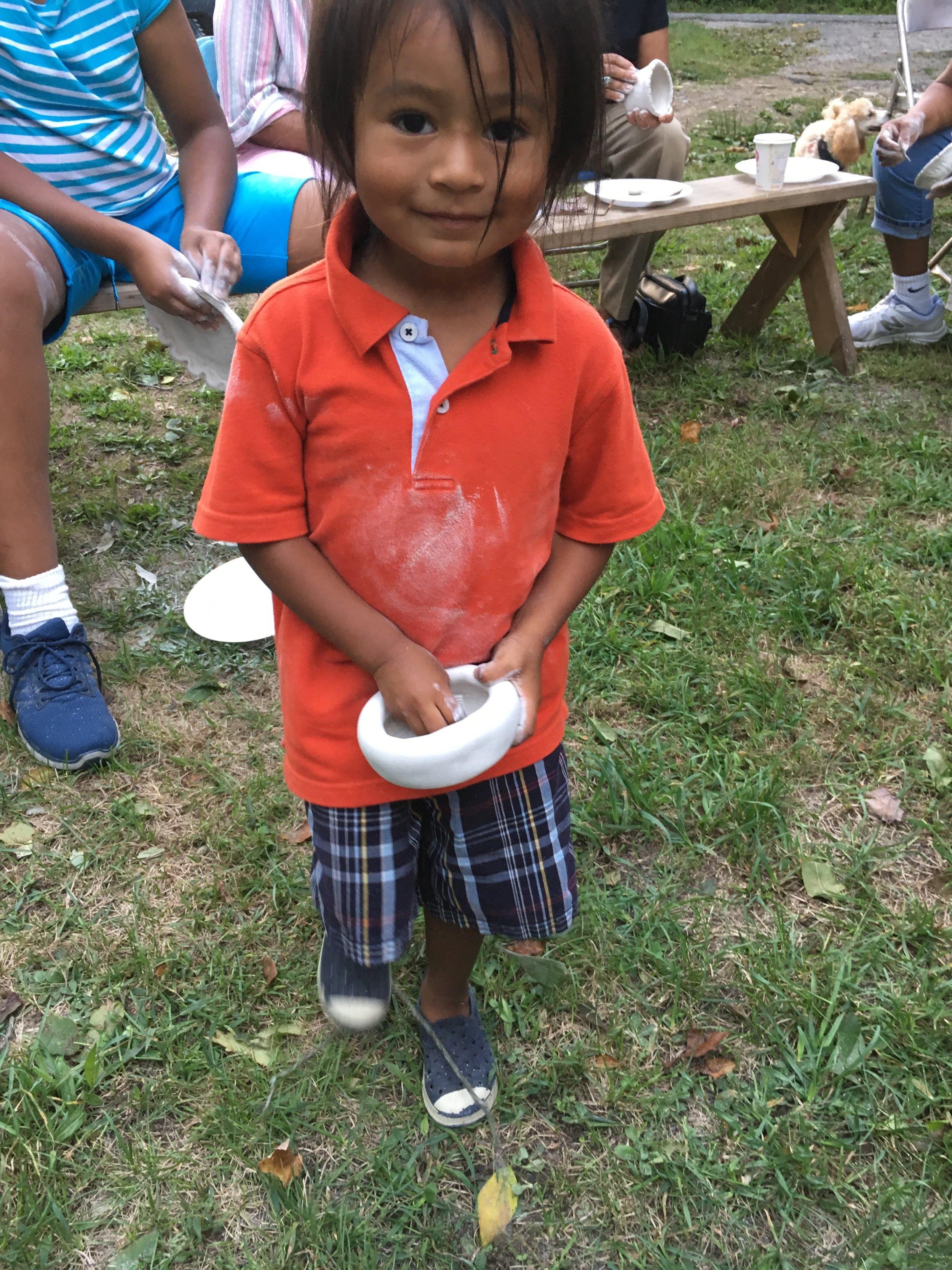 Nikosis LaRose, Narragansett/Ute, polishes a newly made clay bowl