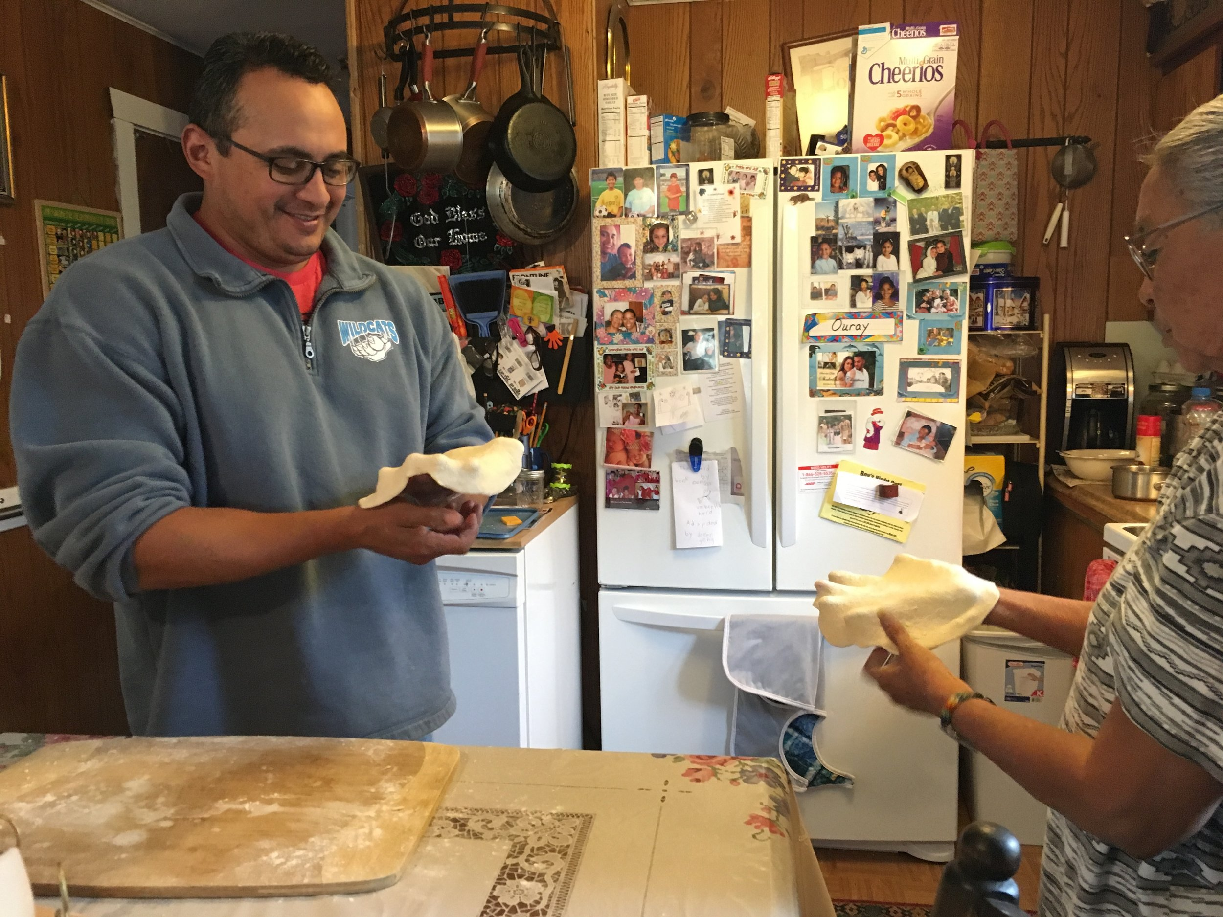Tomaquag's Marketing Associate, Quanah LaRose learning how to make Frybread from his mother.