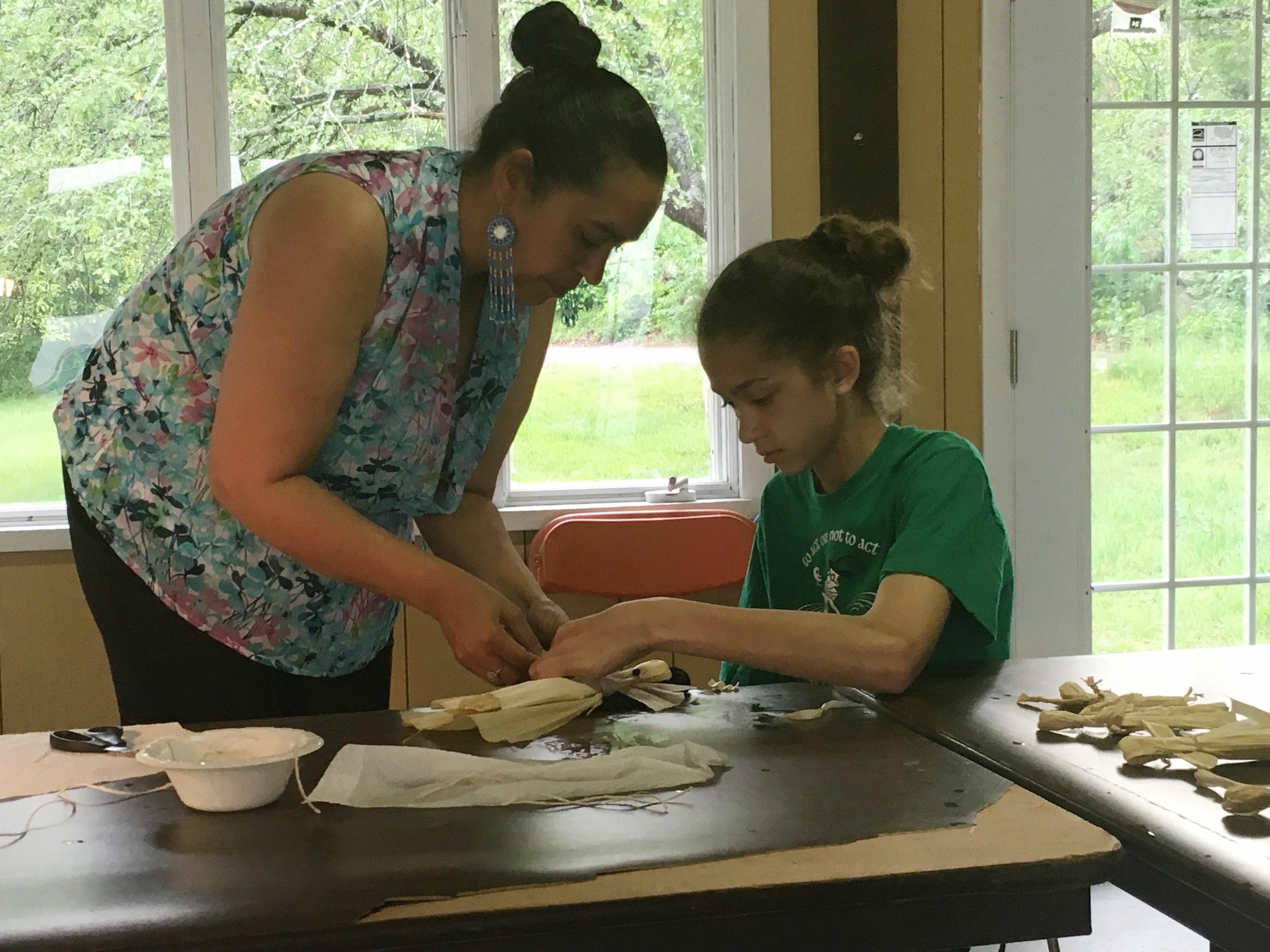 Tomaquag Director Lorén Spears teaches Nkeke Harris, Narragansett, to make a corn husk doll