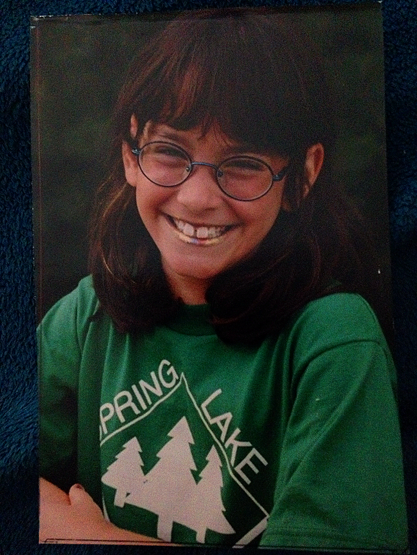 "Here's another photographic gem: Me, about age 7, from Spring Lake Day Camp with four different shades of ""hair mascara"" on my head and matching stripes on my lips."