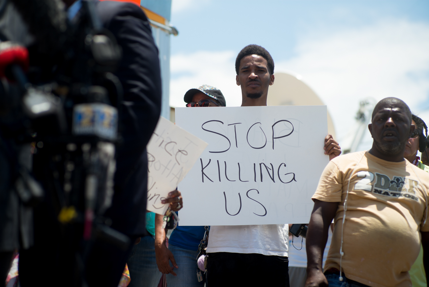A young man holds up a sign as people gather at the scene where Alton Sterling was shot and killed by police.