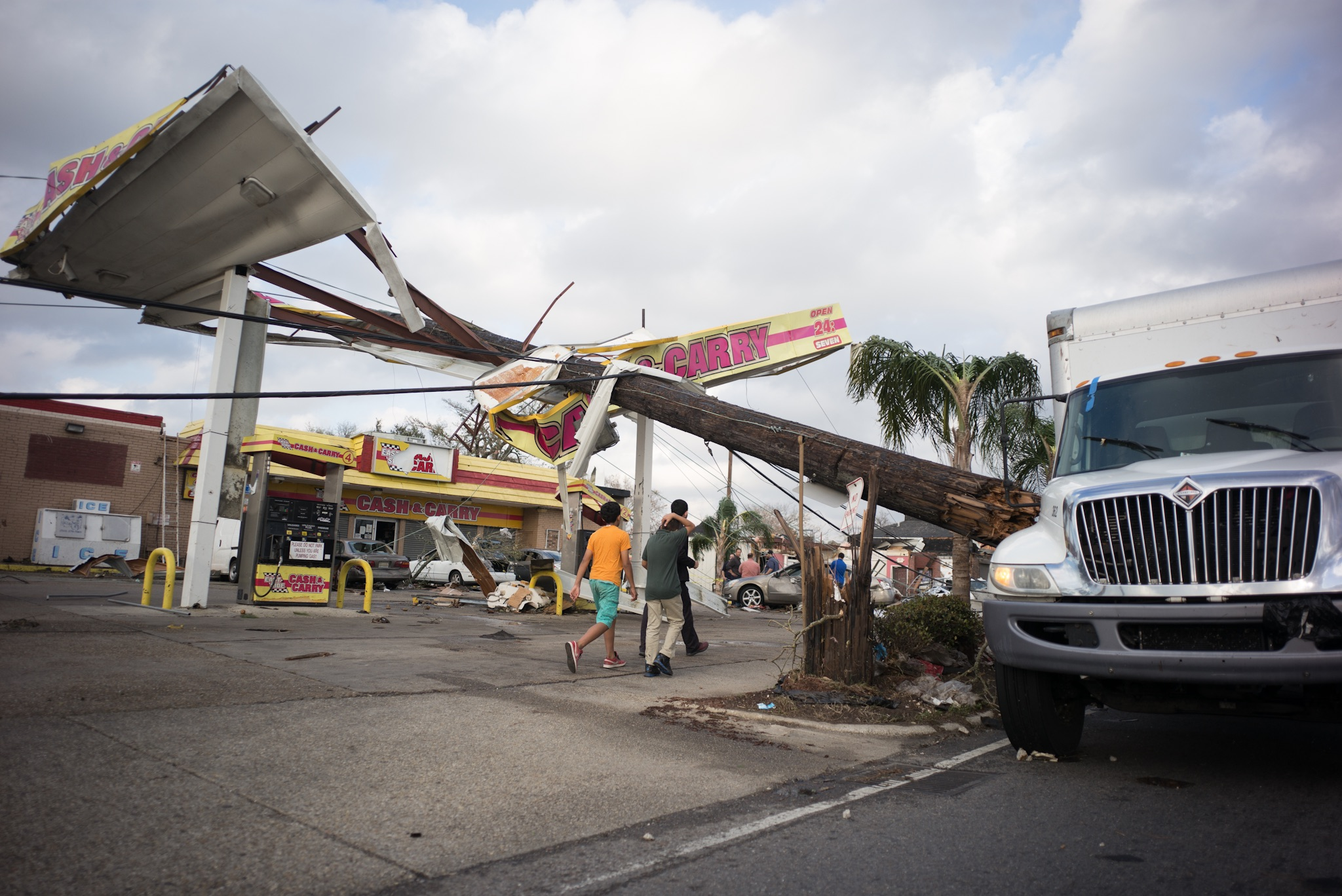 Children walk beneath a downed power pole resting atop a gas station along Chef Menteur Highway in New Orleans East.