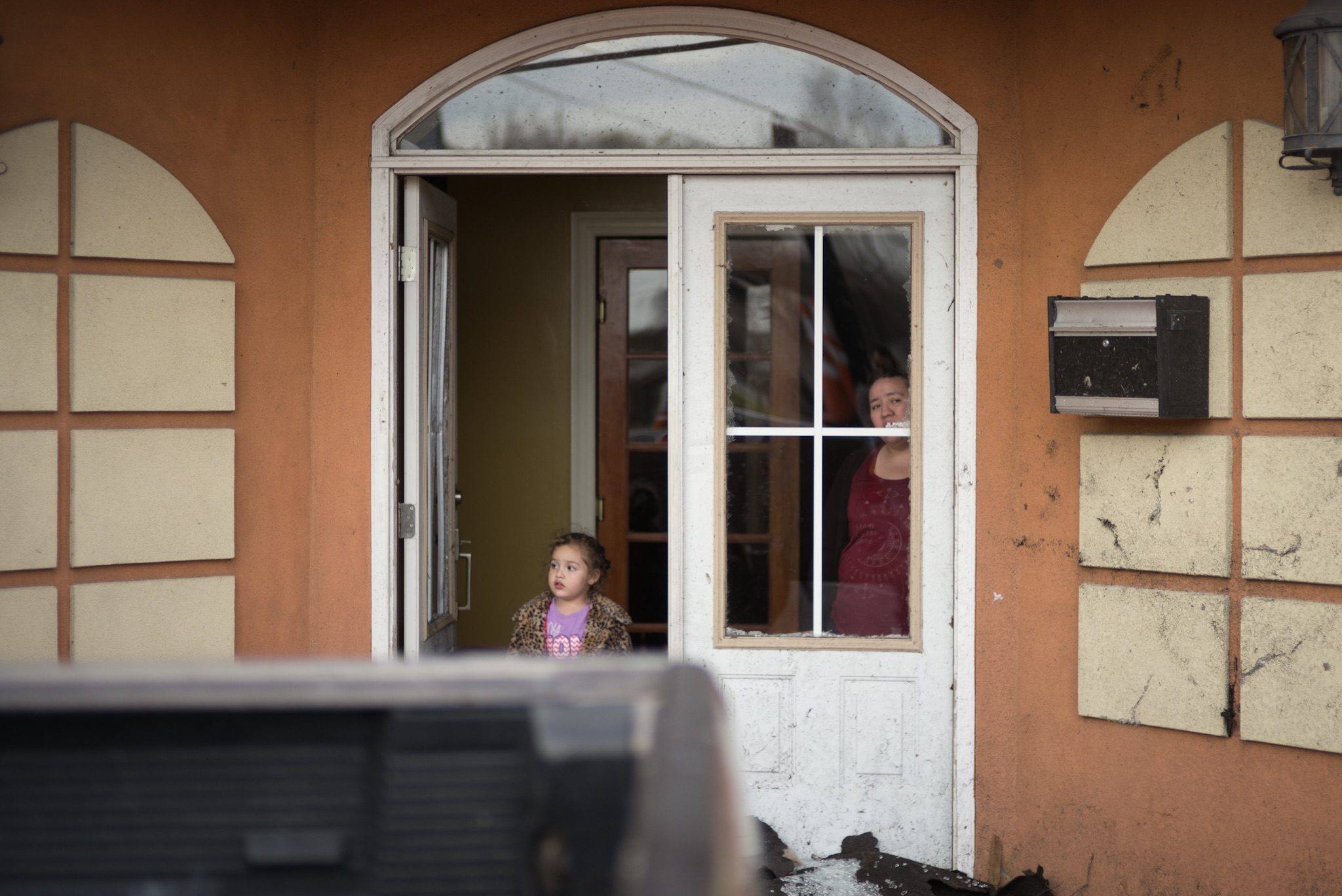 A woman and child observe the damage outside a business after a tornado struck the neighborhood of New Orleans East.