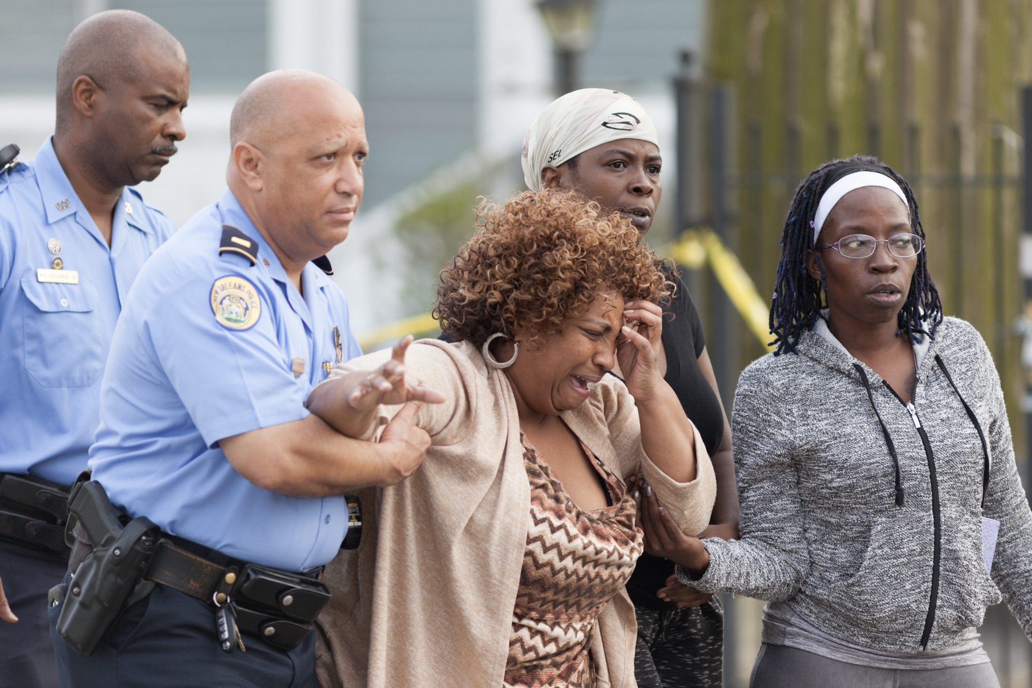 An emotionally distraught woman is assisted by police outside the scene of a triple homicide at 4237 Touro St. in the New Orleans neighborhood of Gentilly where 30-year-old Monique Smith, 10-year-old Justin Simms and 6-year-old Jumyrin Smith were found shot and killed. A fourth victim, A'Miya Smith, age 12, was transported to an area hospital in critical condition.