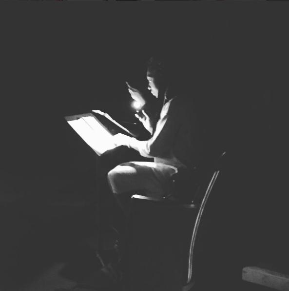 Porscha Shaw reads her script by cell phone light.