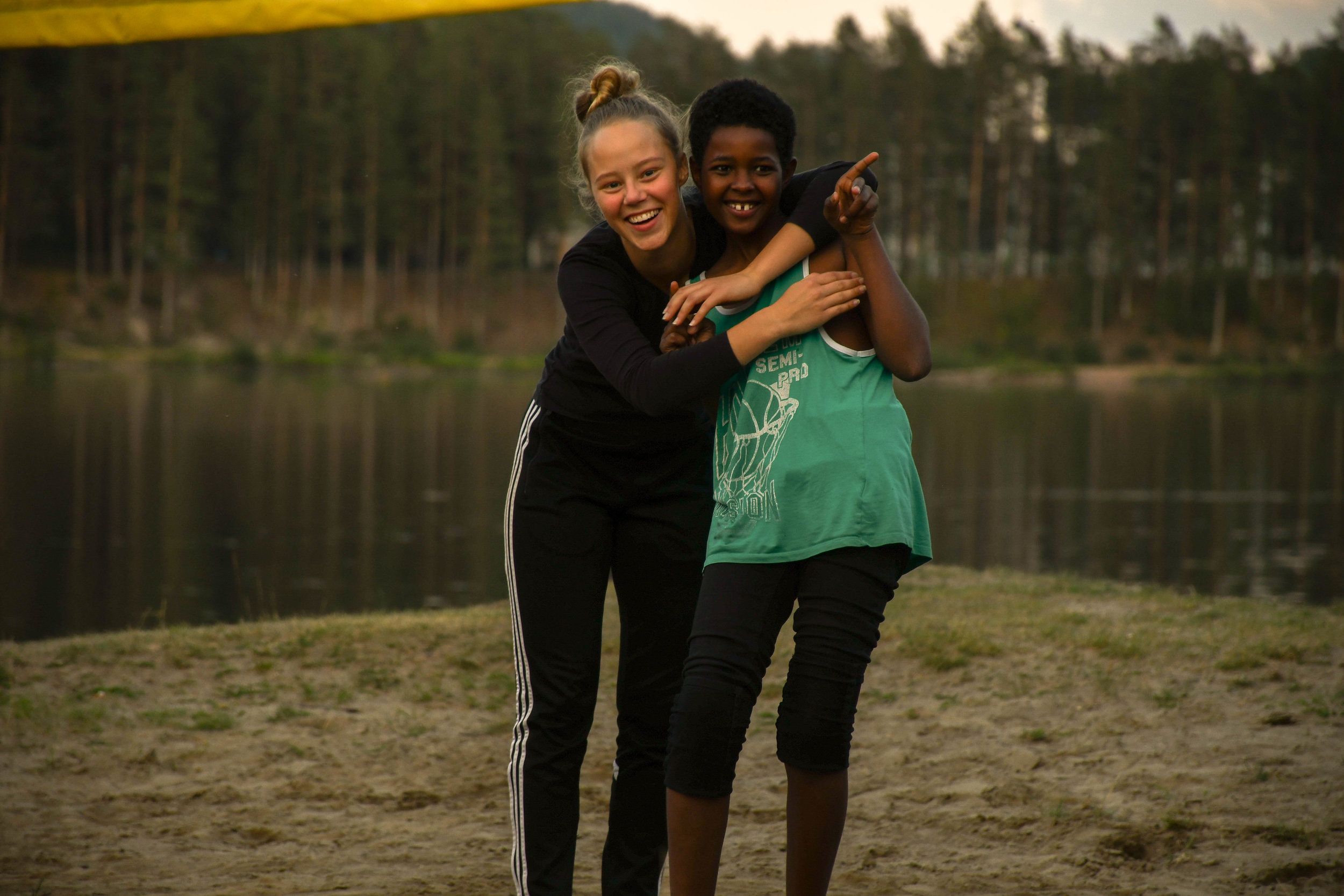 Two of our campers playing volleyball and having fun together at the lake after camp