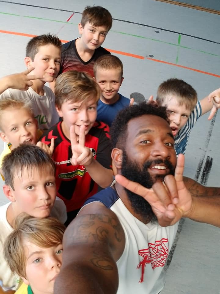One of our players and some of the campers smiling and posing for a selfie