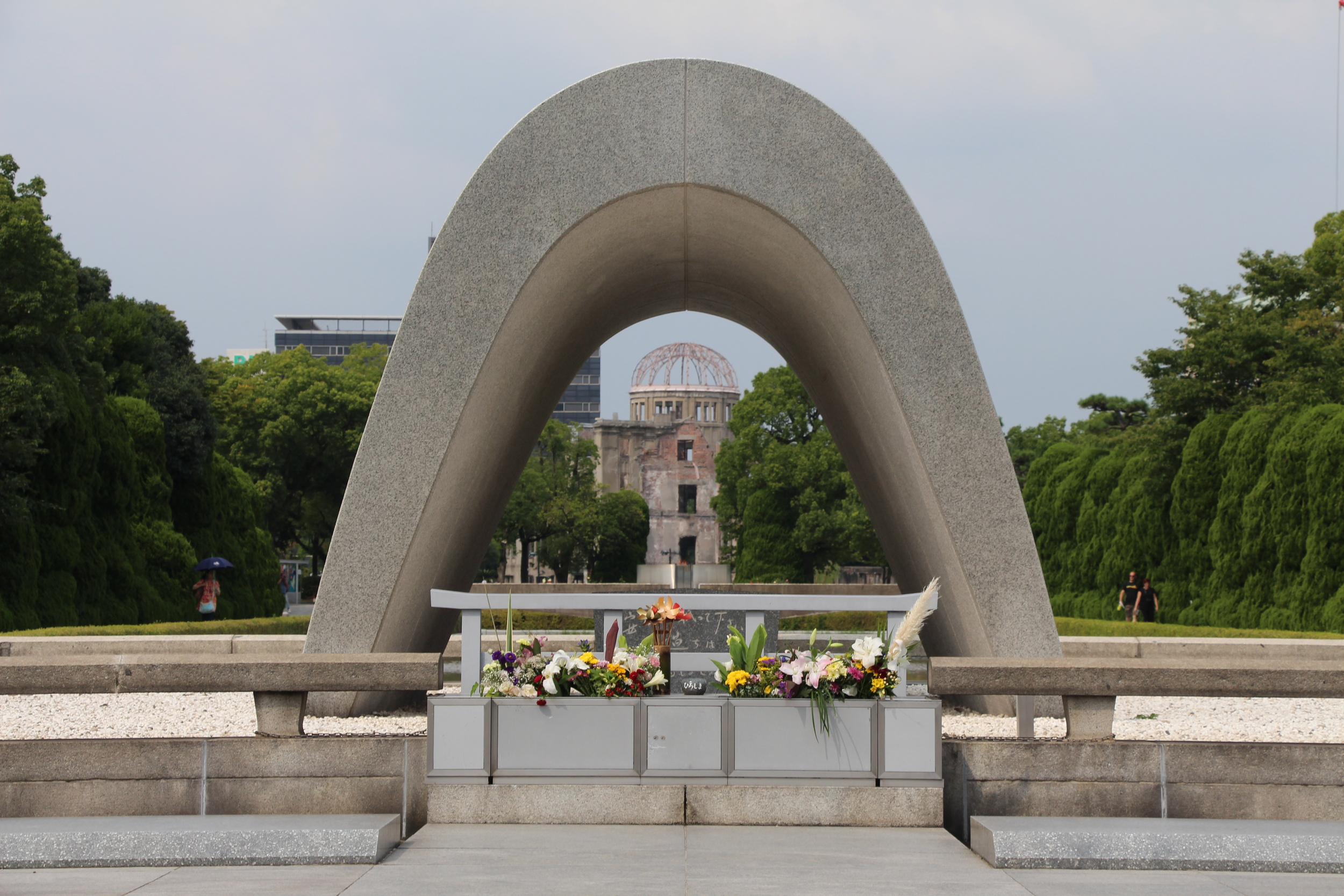The victims' memorial framing the A-bomb Dome and the Peace Flame. The Peace Flame will burn until nuclear weapons are abolished.