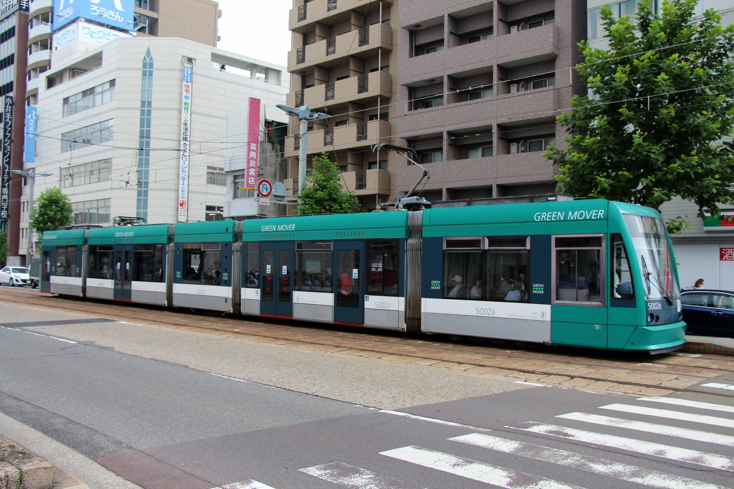 This modern tram car in Hiroshima runs on the same track as the adjacent old tram car.