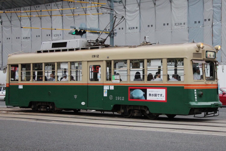 This older tram car in Hiroshima runs on the same track as the adjacent modern tram car.