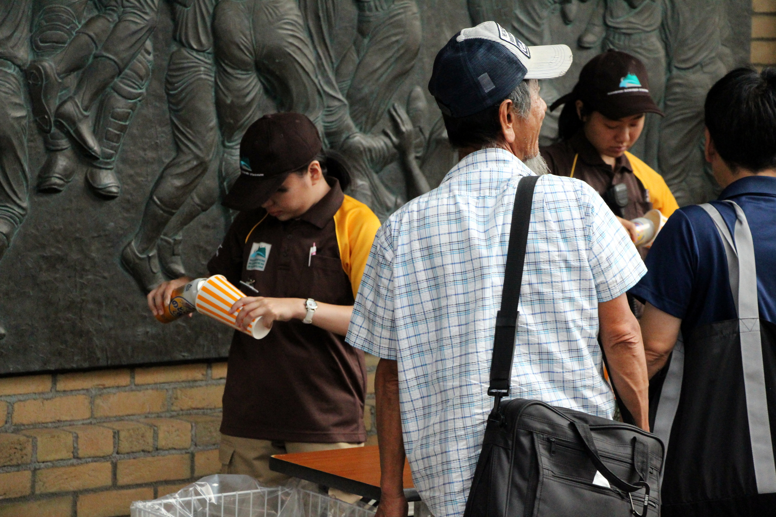 A gate agent at Hanshin Koshien Stadium pours a full tallboy can of beer into a cup for a Tiger's fan before he enters the park.