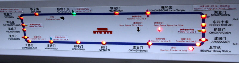 """A picture of the in car map on Line 2, the older of the two loop lines in the Beijing subway system. (Click to enlarge) The green light is the next station. Transfer stations are clearly marked. Note the light under the sign """"Door Opens Opposite Side"""" signifying that the opposite doors will open at the next station. Also note the """"Counter-Clockwise Loop"""" light signifying the direction the train is traveling. The red gate in the middle of map denotes Tiananmen Gate at the very center of the city. This icon appears on full subway system maps and maps of lines that go near the square."""