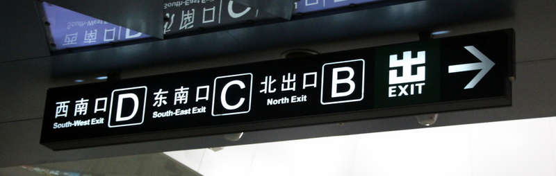 Station exit signage not only features the letter of the exit, but the cardinal direction as well