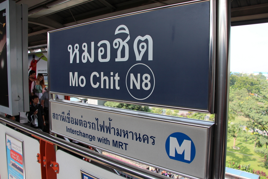 The station sign at Mo Chit, a stop on the BTS Skytrain. Note that the station has a number (N8).The interchange with MRT sign indicates a nearby MRT subway station.