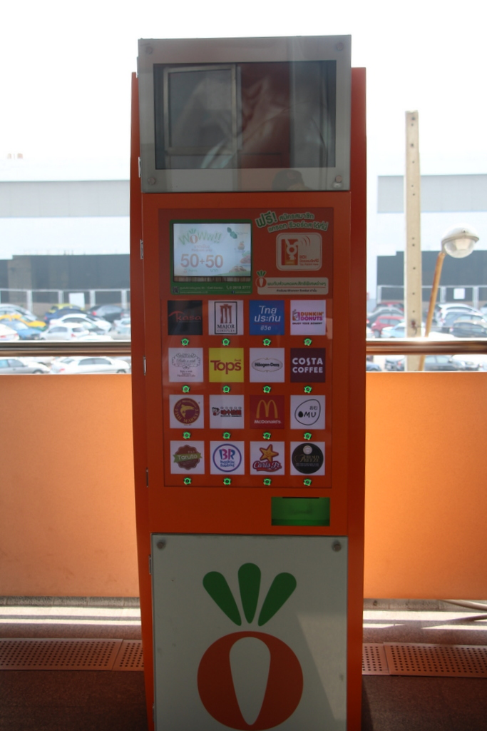 A coupon kiosk for Carrot Reward members at a BTS station. All the logos you see are partner companies that you can print multiple coupons to from this kiosk, including McDonalds, Dunkin' Donuts, and Major Cineplex, a local movie theater chain.