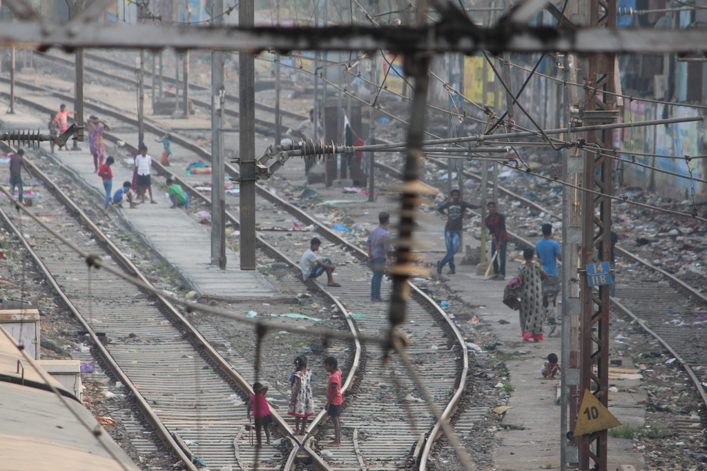 Kids making do with what they've got by playing cricket on the railroad tracks.