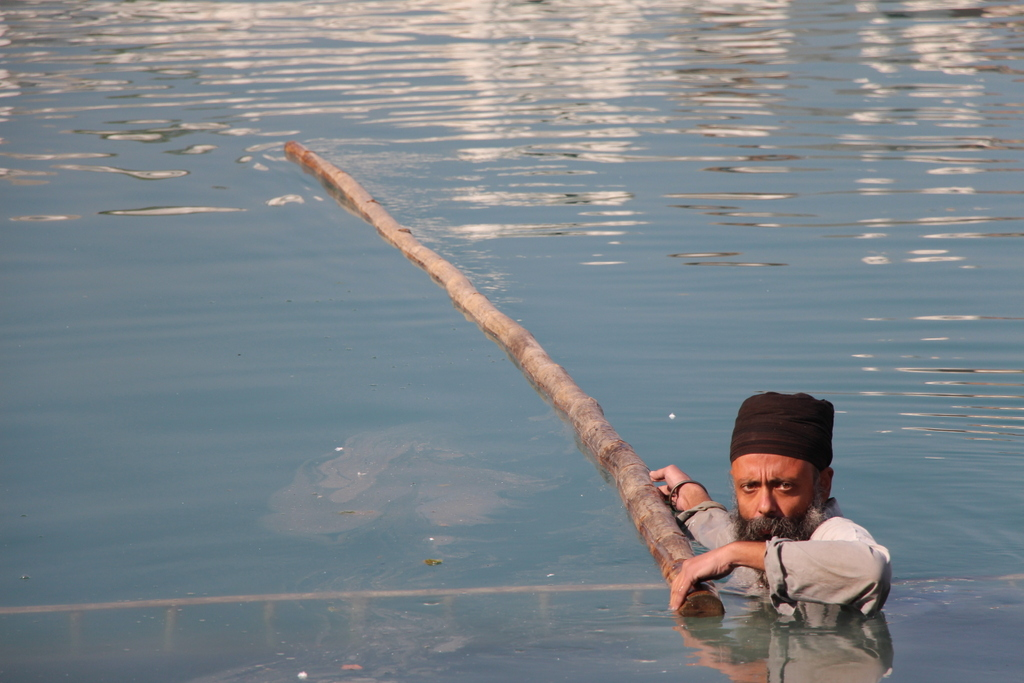 We saw several men like this in the water from time to time who would use the pole to skim off any dirt or grime that was floating on the water
