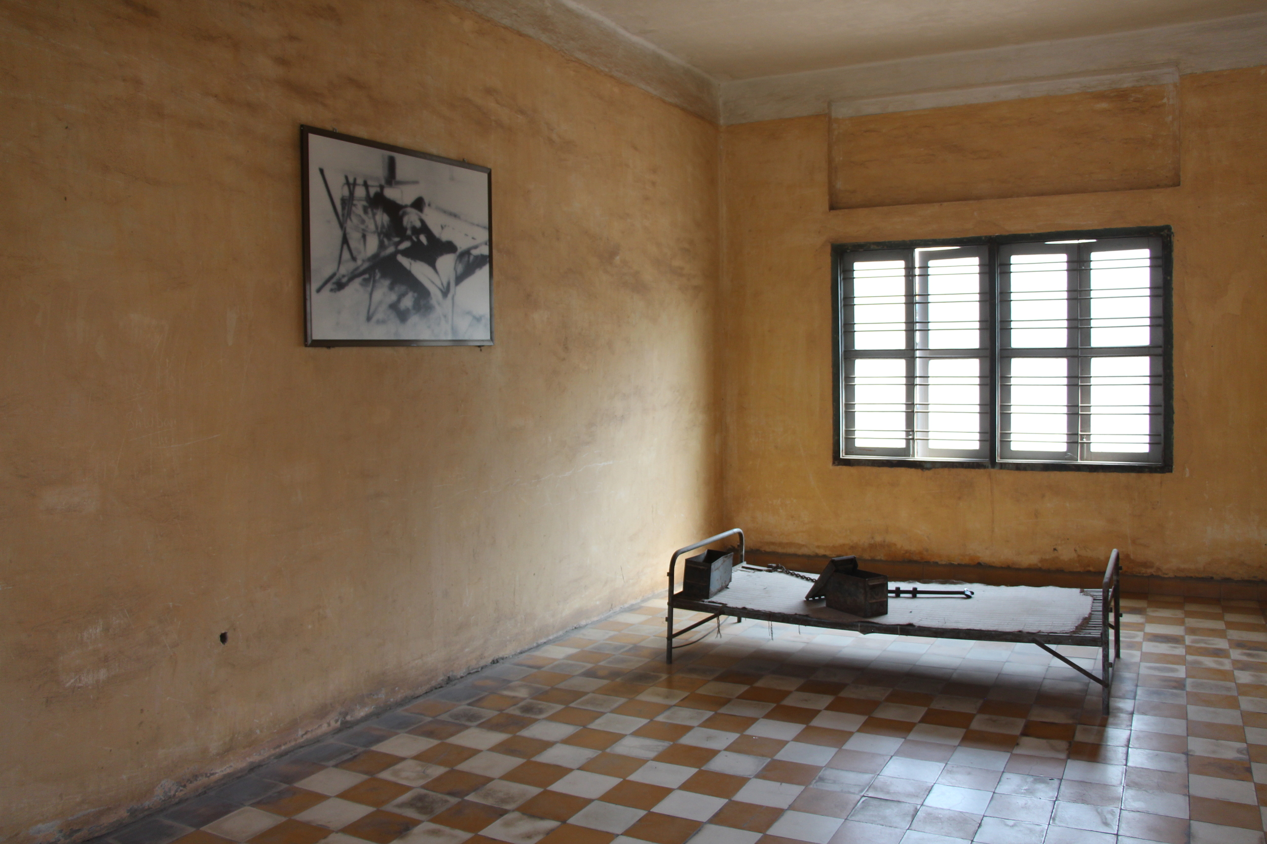 Large rooms like this were used to harbor high-ranking officials before they were tortured and killed. Leg shackles and a torture device are visible on the bed.
