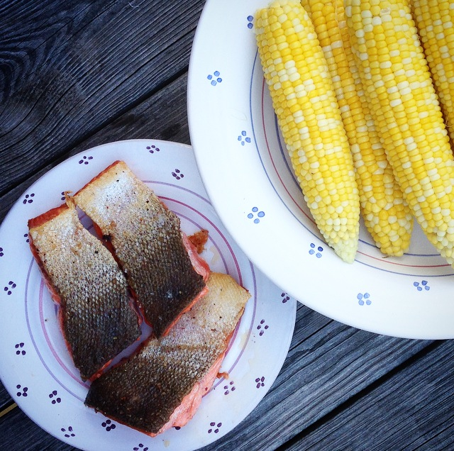 Dinner is served - crispy salmon filets and local sweet corn with butter