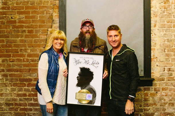 "Crowder is honored with an RIAA Gold Certification plaque for David Crowder*Band's digital single ""How He Loves"" with sixstepsrecords' Shelley Giglio and Mike McCloskey."