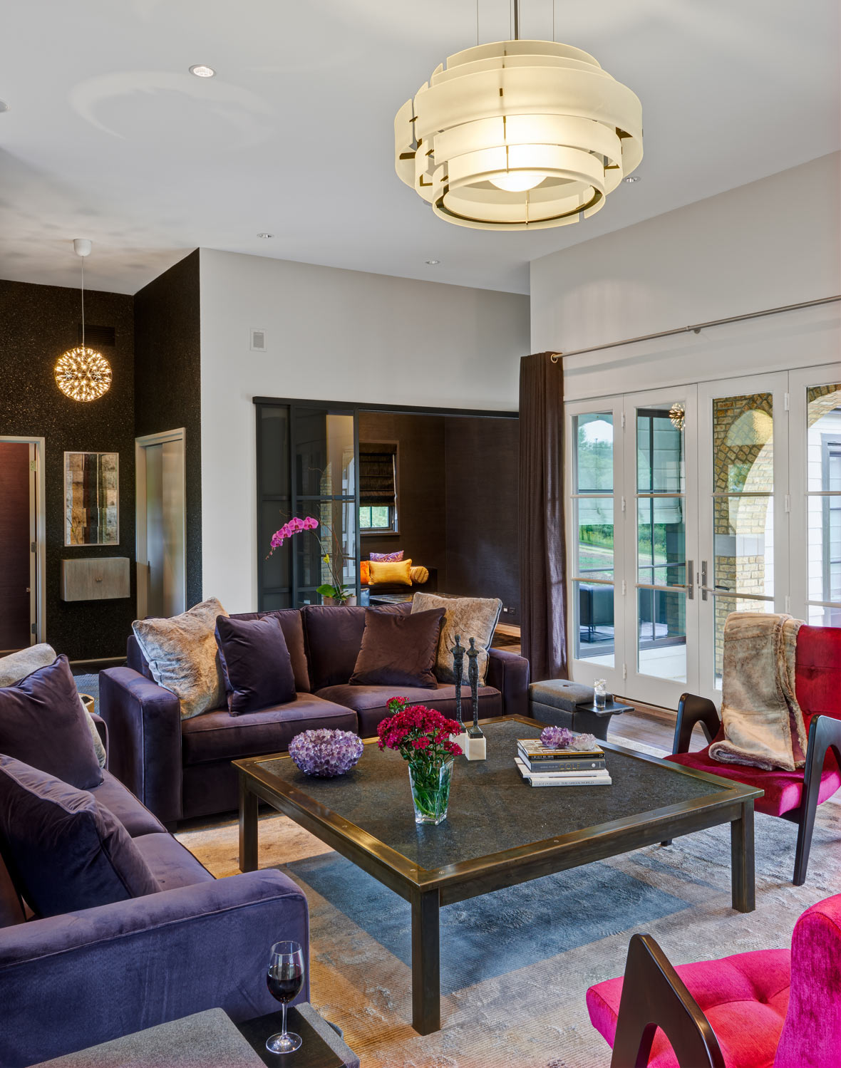 Fort Sheridan Ranch - Family Room   Flanked by large windows. Plum velvet sofas andfuschiamidcentury chairs. The coffee table is steel with a honed granite insert andaccessorizedwith an amethystcrystal bowl.  Featured COUEF pieces:  Madison Classic Ottoman , Clark Throw , Rex Toss Pillows